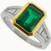 An Emerald cut Emerald Solitaire Ring with Diamond Set shoulders